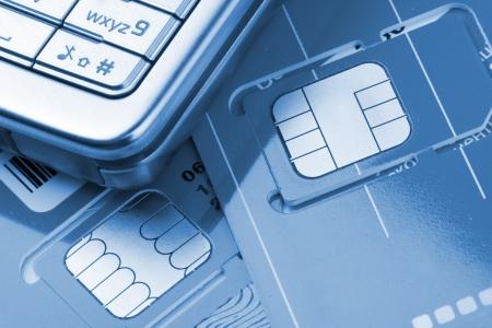Primer plano de tel�fono m�vil con las tarjetas SIM. Tonos de azul Foto de archivo