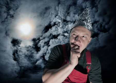 Scared suspecting man wearing a foil hat against dark stormy sky Stock Photo - 18055809