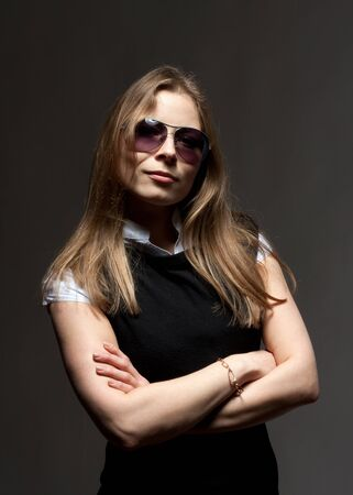 Portrait of beautiful woman in glasses with crossed arms photo
