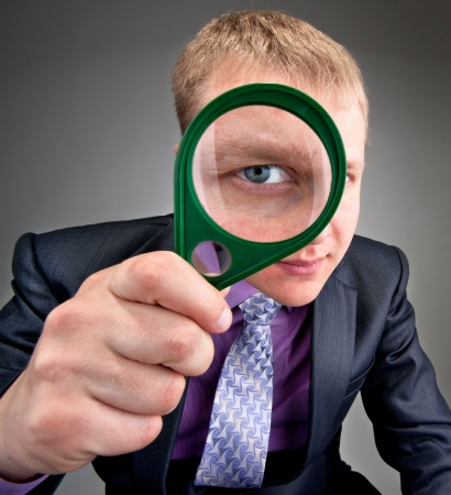 worried businessman: Worried businessman looking to you through magnifier lens Stock Photo
