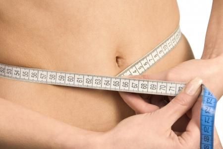 Beautiful woman's stomach with measure. Isolated on white Stock Photo - 18033220