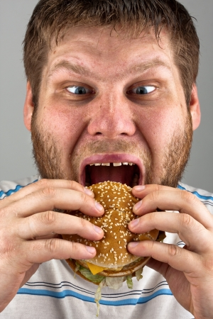 Close-up of bearded man eating juicy hamburger photo