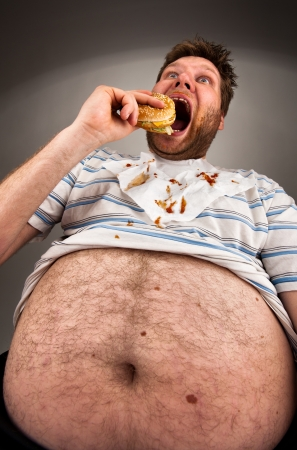 Portrait of expressive fat man eating burger
