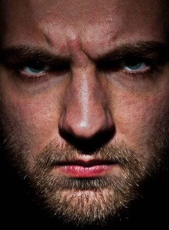 Close-up portrait of angry bearded young man photo