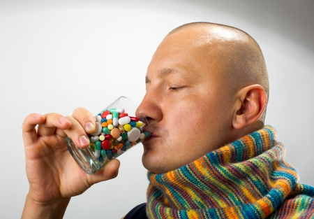 Ill man drinking cocktail of colorful pills Stock Photo - 18055559
