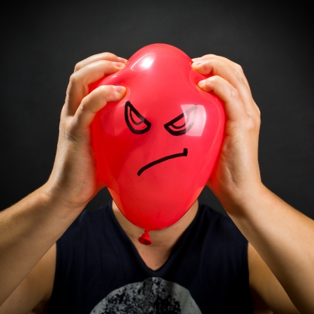 squeezing: Man squeezing red balloon with angry smiley