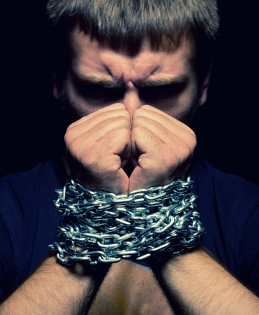 Angry man with chained hands photo