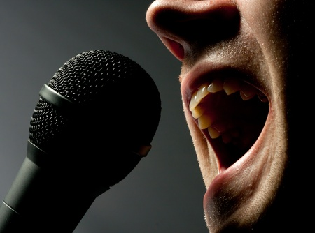 Close-up of man singing to microphone in dark photo