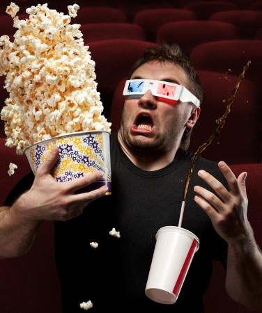 horror movies: Portrait of very scared man watching 3D movie, drinking cola and eating popcorn Stock Photo
