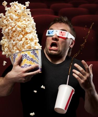 Retrato de hombre muy asustado viendo pel�cula en 3D, el consumo de refrescos de cola y comiendo palomitas de ma�z Foto de archivo