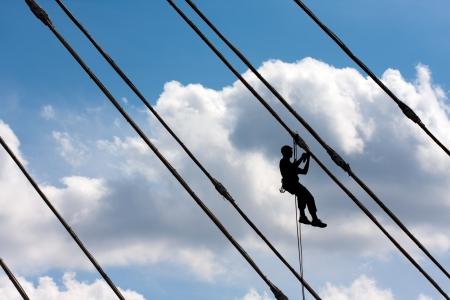 rope bridge: Silhouette of construction climber against blue sky