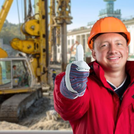 Happy worker against construction site photo
