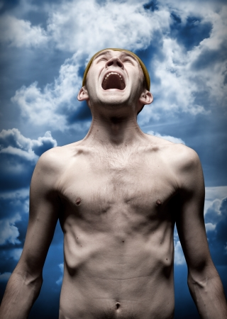 terror: Portrait of despaired screaming man against dramatic sky Stock Photo