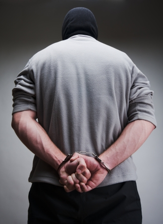 consequence: Big criminal locked in handcuffs. Terrorist in balaclava Stock Photo