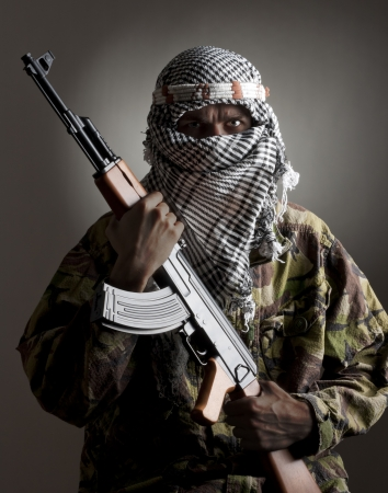 Portrait of serious middle eastern man with AK-47 photo