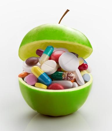 doses: Open rijpe appel vol kleurrijke medicijnen Stockfoto