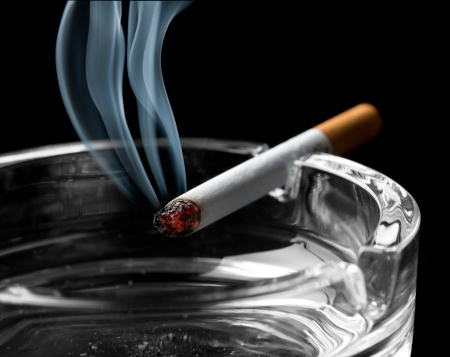 rudeness: Closeup of cigarette on ashtray with a beautiful wisp of smoke