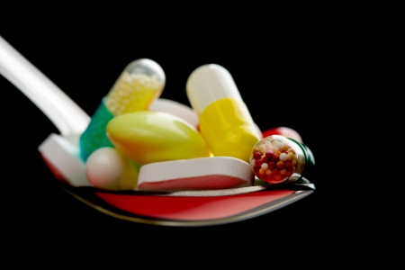Spoon full of various pills. Isolated on black Stock Photo - 18072628
