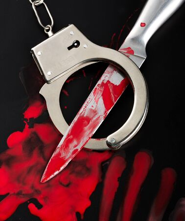 bloody: Knife and handcuffs in blood Stock Photo