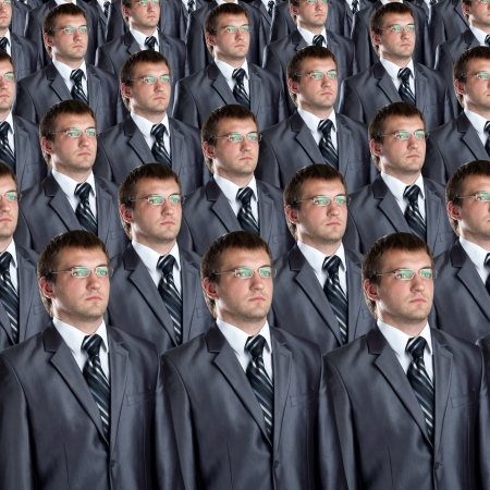 Many identical businessmen clones. Businessman production concept photo