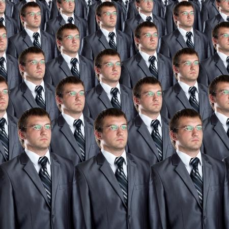 Muchos hombres de negocios clones idénticos. Empresario concepto de producción