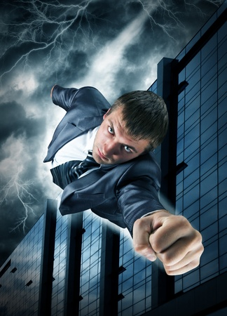 man flying: Superhero businessman flying over downtown in thunderstorm