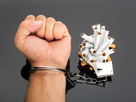 Addict hand locked to cigarettes by handcuffs Stock Photo - 18073507
