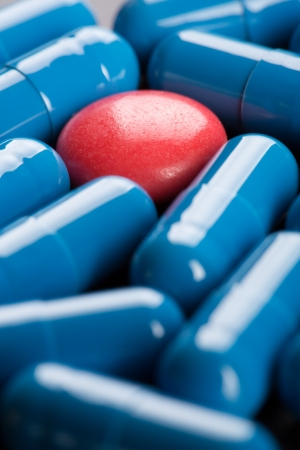 Special red pill between blue capsules Stock Photo - 18074788