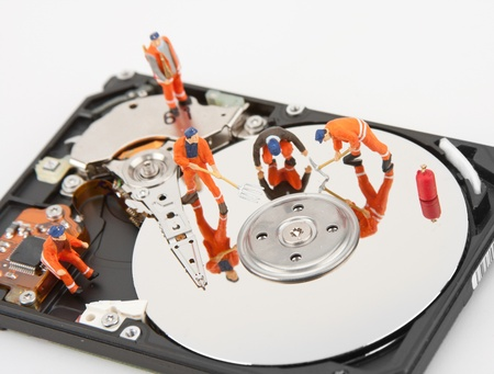 IT support. Workers repairing hard disk drive photo