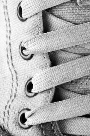 plimsoll: Close-up of running shoe laces. In BW