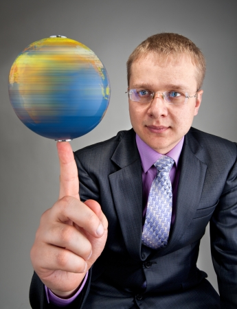 Portrait of serious businessman spinning the world globe on finger photo