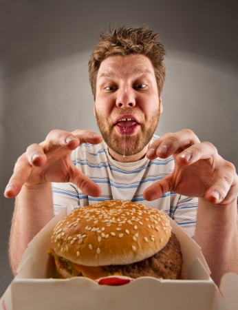 saliva: Portrait of happy man with leaking saliva preparing to eat burger Stock Photo