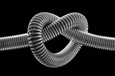 knotted: Close-up of knotted metal spring. In BW