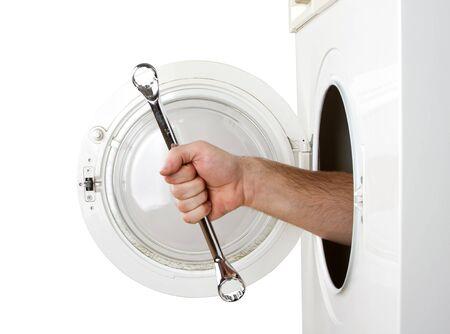 Repairman servicing washing machine. Isolated on white photo