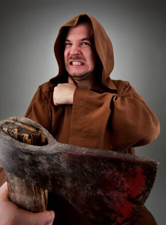 Furious medieval executioner with big bloody axe photo