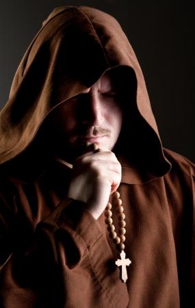 Portret van de middeleeuwse monnik met kruis rozenkrans in de schaduw