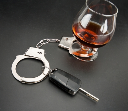 sobriety: Car key locked to glass of alcohol by handcuffs