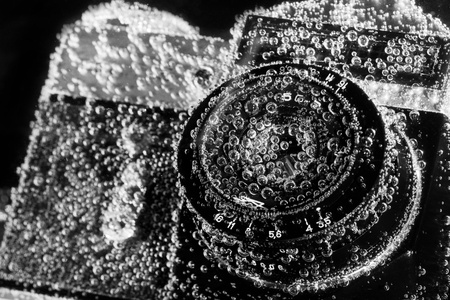slr cameras: Close-up of old drowned camera under water Stock Photo