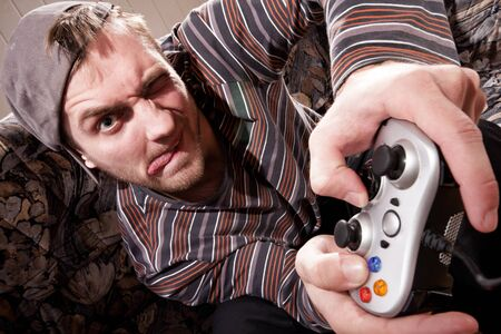 Excited man with joystick playing video games at home photo