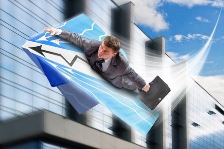 man flying: Businessman on paper airplane flying over downtown Stock Photo