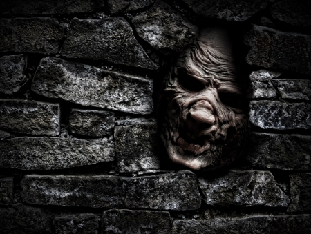 horrors: Horror monster looking out from hole in the wall Stock Photo