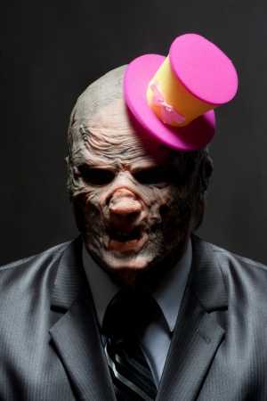 Sad monster in business suit with funny pink hat photo