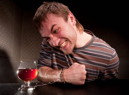 drinking problem: Alcoholic locked to glass of alcohol by handcuffs