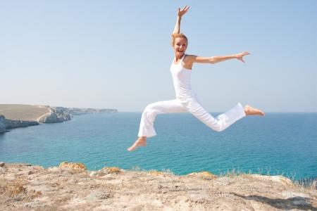 tissu blanc: Femme sautant dans un tissu blanc contre la mer