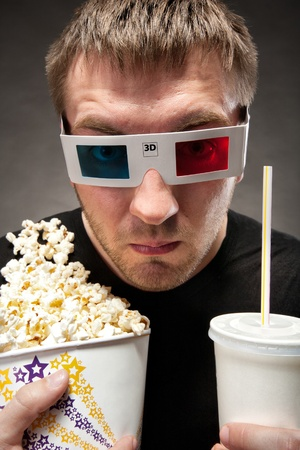 ridiculous: Funny man watching 3D movie, drinking soda and eating popcorn Stock Photo