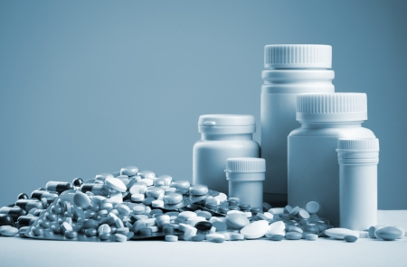 blue toned: Various pills, capsules, dragee and white bottles. Toned Stock Photo