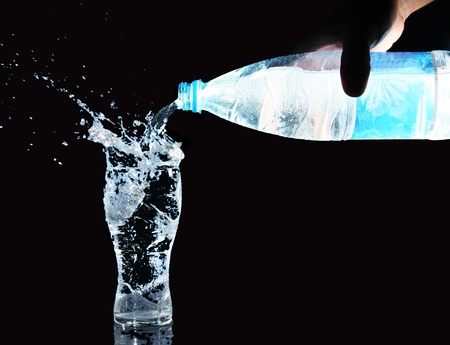 overflowing: Pouring water from bottle into glass Stock Photo