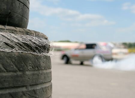 smoke stack: Used racing tires with sport car on background
