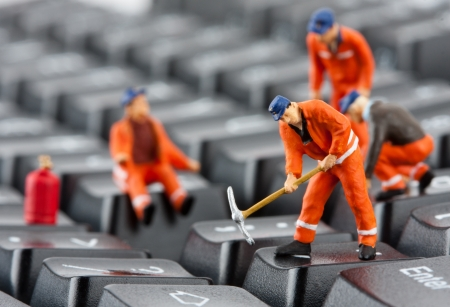 Small figurines of workers repairing computer keyboard Stock Photo