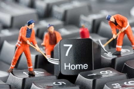 Small figurines of workers repairing computer keyboard Imagens
